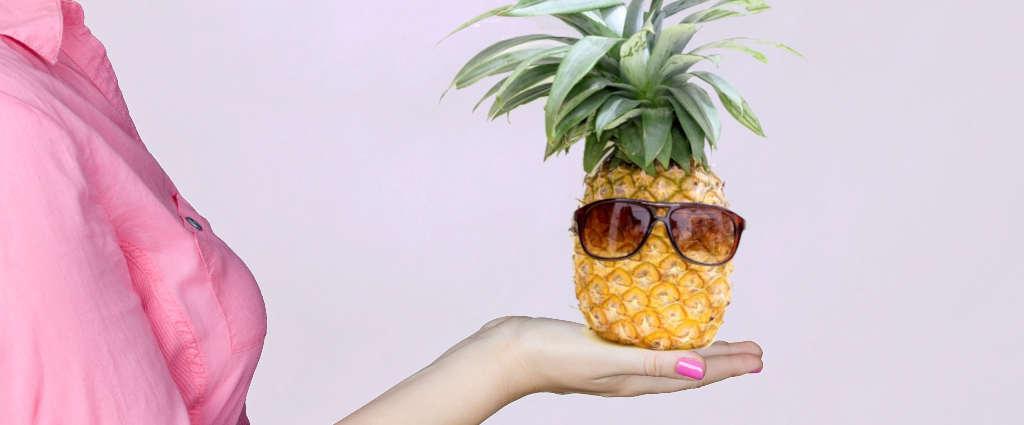 boucles d'oreilles ananas, femme tenant dans sa main une broméliacée