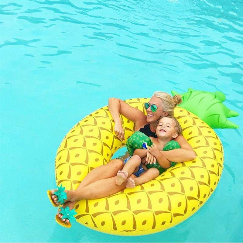 bouée en forme d'ananas dans une piscine avec un adulte et un enfant