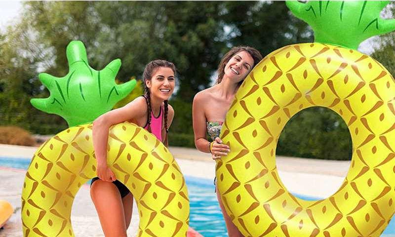 bouee ananas geante avec deux filles au bord d'une piscine