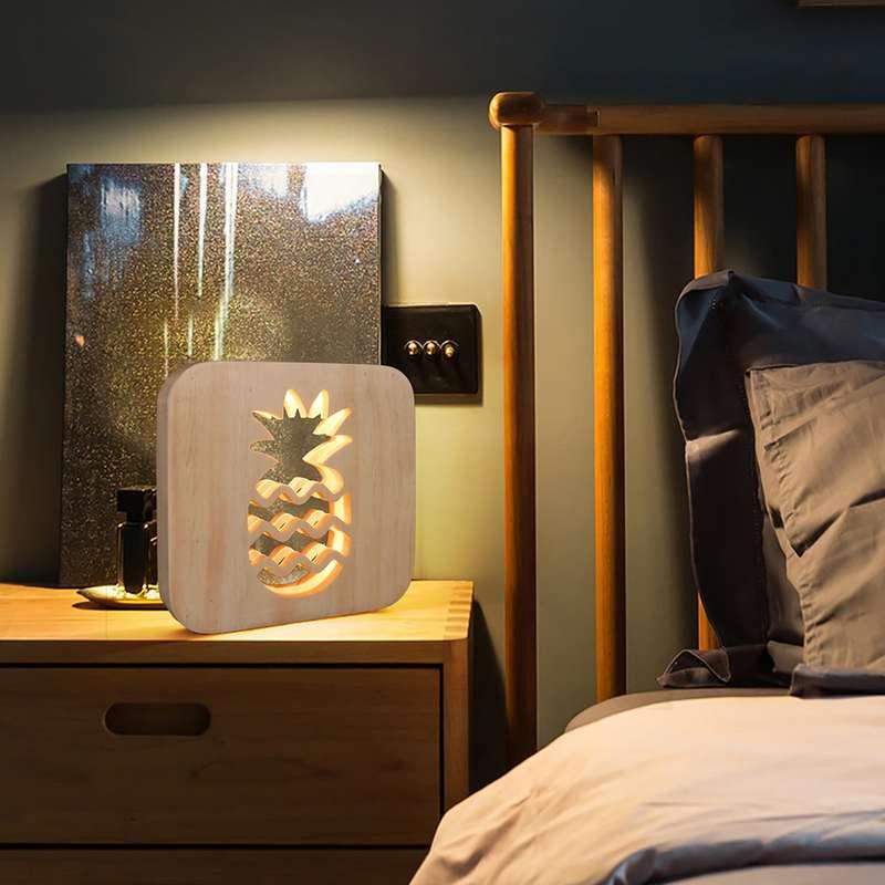 lampe ananas en bois posée sur le coin d'un meuble dans une chambre
