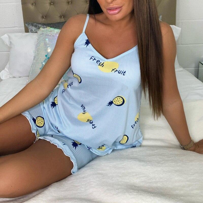 pyjama short motif ananas bleu porté par femme assise sur un lit